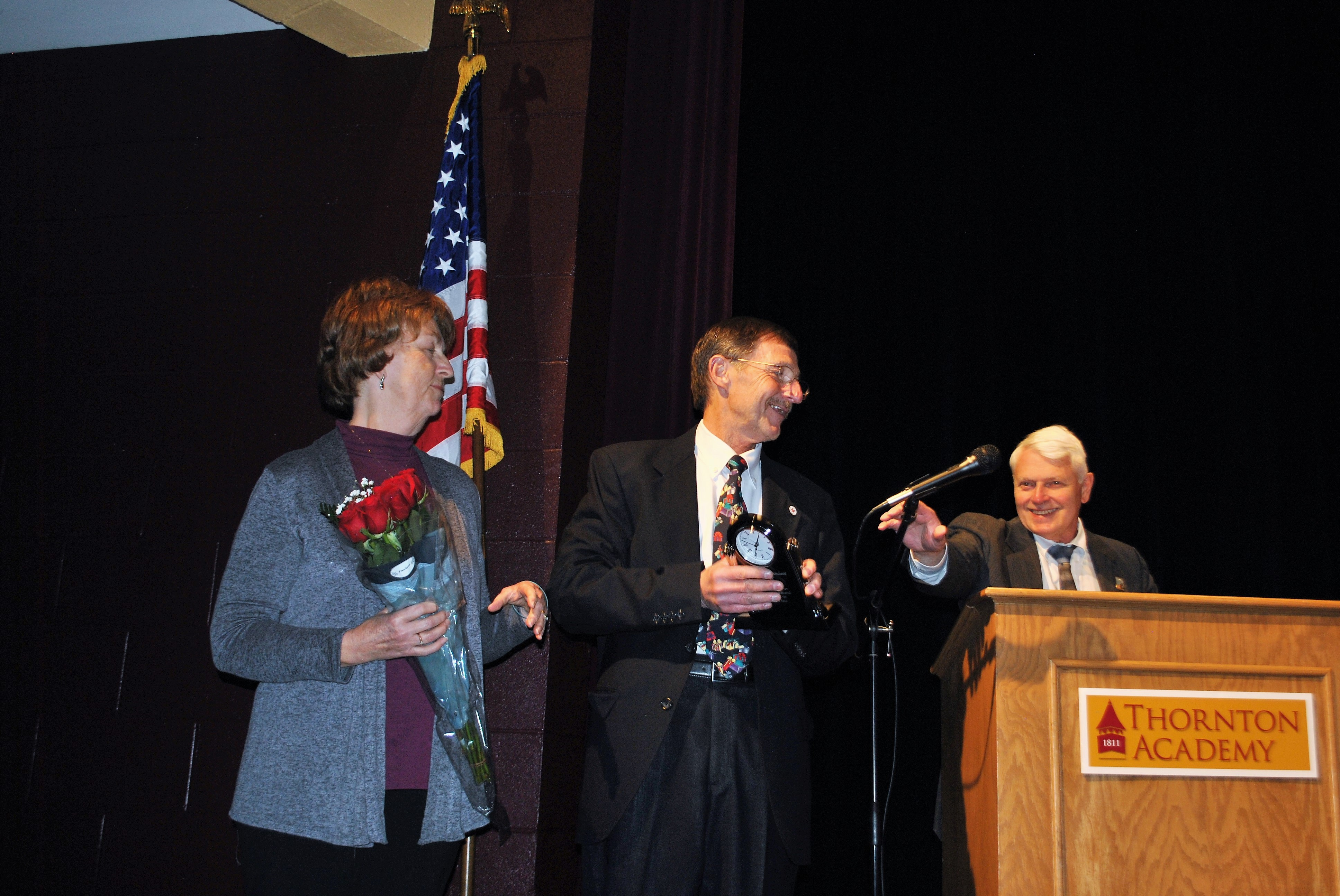 Saco Mayor Marston Lovell, right, hands a microphone to outgoing mayor Ron Michaud at the inauguration ceremony at Thornton Academy on Monday night. Standing next to Michaud is his wife, Hilda. LIZ GOTTHELF/Journal Tribune
