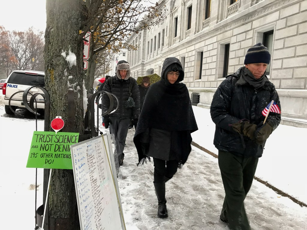 """Members of the Portland Friends Meeting Quaker community and other protesters express their disapproval of the Trump administration's planned withdrawal from the Paris climate agreement with a """"walking vigil"""" around the federal courthouse in Portland on Tuesday. Participants walked around the block 196 times, once for each nation that has signed on to the accord."""
