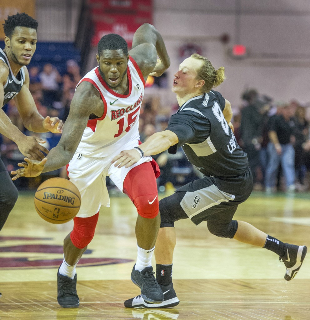 Maine's Anthony Bennett pushes the ball upcourt ahead of Austin's Jeff Ledbetter in Monday night's game at the Portland Expo.