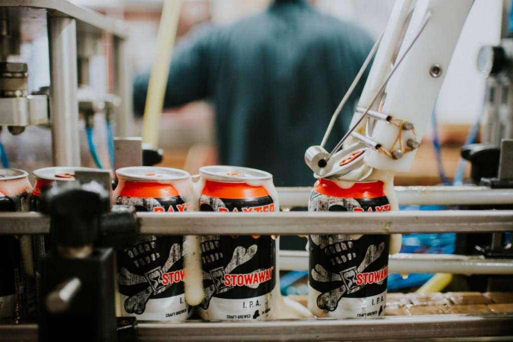Cans of Baxter's Stowaway IPA are topped off at their Lewiston brewery. Baxter opened 7 years ago in Lewiston's Bates Mill and brewed more than 15,000 barrels of craft beer last year.