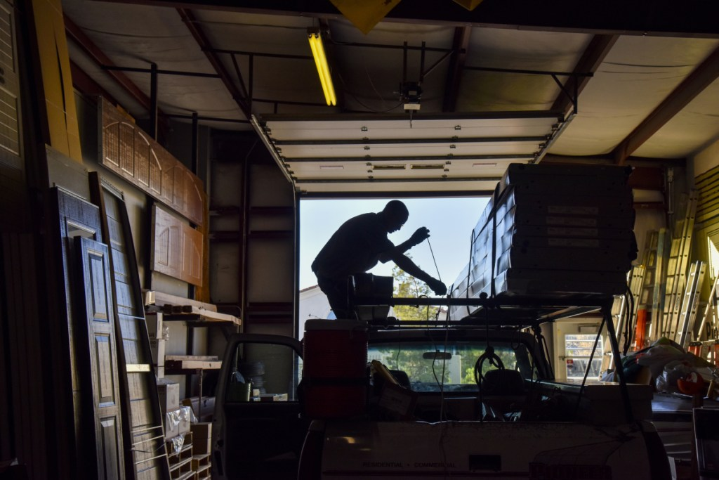 Ian Black loads a truck in preparation for a day of installing garage doors for Pioneer Overhead Door in Las Vegas. A convicted burglar, he spends his nights in a work-release facility and works at Pioneer by day.