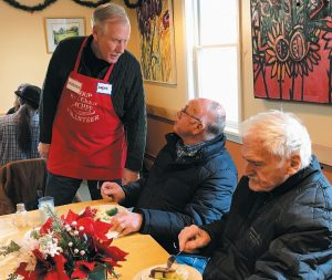U.S. SEN. ANGUS KING of Brunswick talks with Carl Brown of Bath on Monday while clearing tables at the Mid Coast Hunger Prevention Program's soup kitchen.