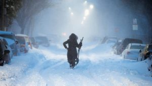A WOMAN WALKS DOWN snow-covered Maverick Street in the East Boston neighborhood of Boston on Thursday as a huge winter storm roared up the East Coast with hurricane-force winds, heavy snow and coastal flooding.