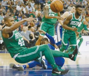 BOSTON CELTICS forward-center Al Horford, left, goes down on the floor during an NBA basketball game between the Boston Celtics and the Philadelphia 76ers at the O2 Arena in London on Thursday. The Celtics won, 114-103.