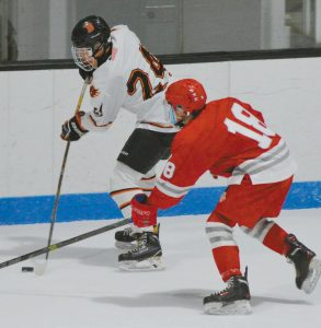 THE BRUNSWICK DRAGONS took on the South Portland/Freeport/Waynflete team in boys hockey Monday night. Pictured at top, Dragon Henry Burnham (24) skates ahead of Red Riot Bradley McMains (18) with the puck. Above, Aiden Snell (7) intercepts the puck off the boards from Caleb Rowland (6). The visitors downed Brunswick, 5-2, at Watson Arena.