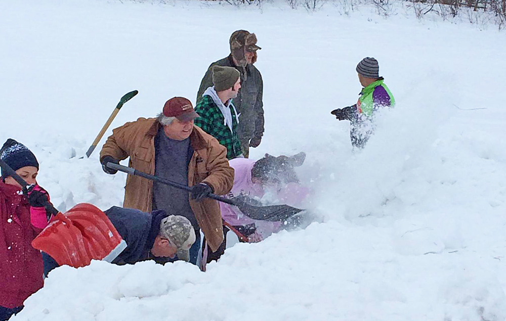 This photo posted on Facebook by Barbetta Ann Bowker Turner shows passersby on Route shoveling out the baby moose.