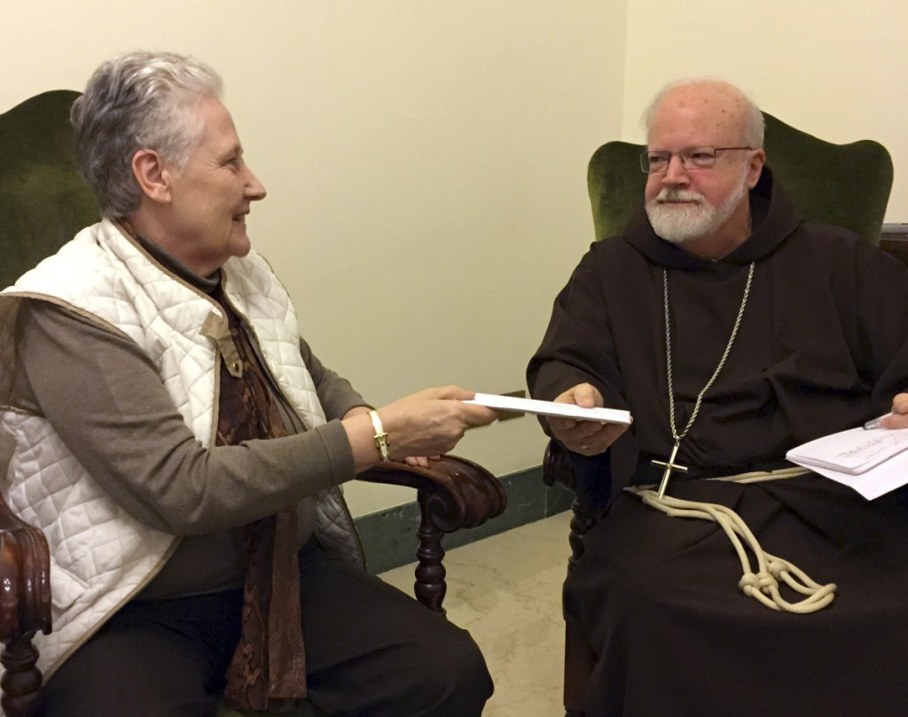 Marie Collins, part of the pope's sex-abuse commission, hands a letter in 2015 to Cardinal Sean O'Malley, Pope Francis' top adviser, about the abuse of Juan Carlos Cruz.