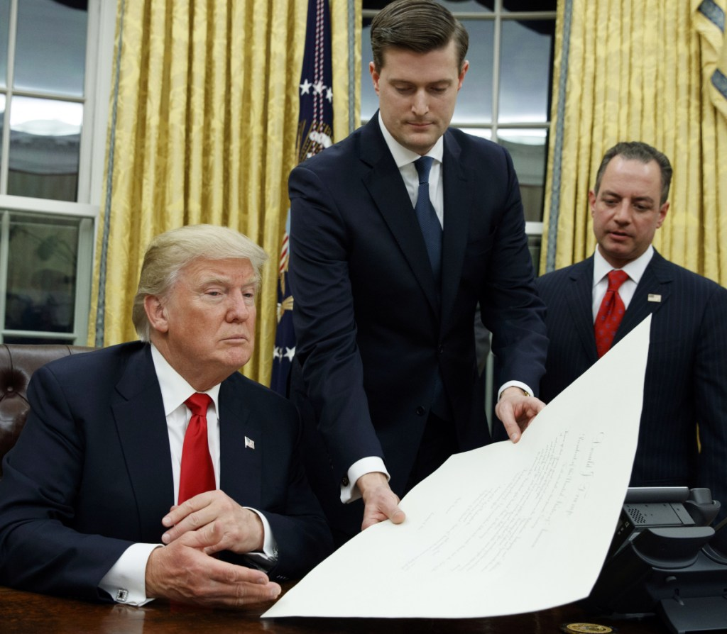 In this Jan. 20, 2017 file photo, White House Staff Secretary Rob Porter, center, hands President Donald Trump a confirmation order for James Mattis as defense secretary, in the Oval Office of the White House in Washington, as White House Chief of Staff Reince Priebus, right, watches.  Porter is stepping down following allegations of domestic abuse by his two ex-wives.