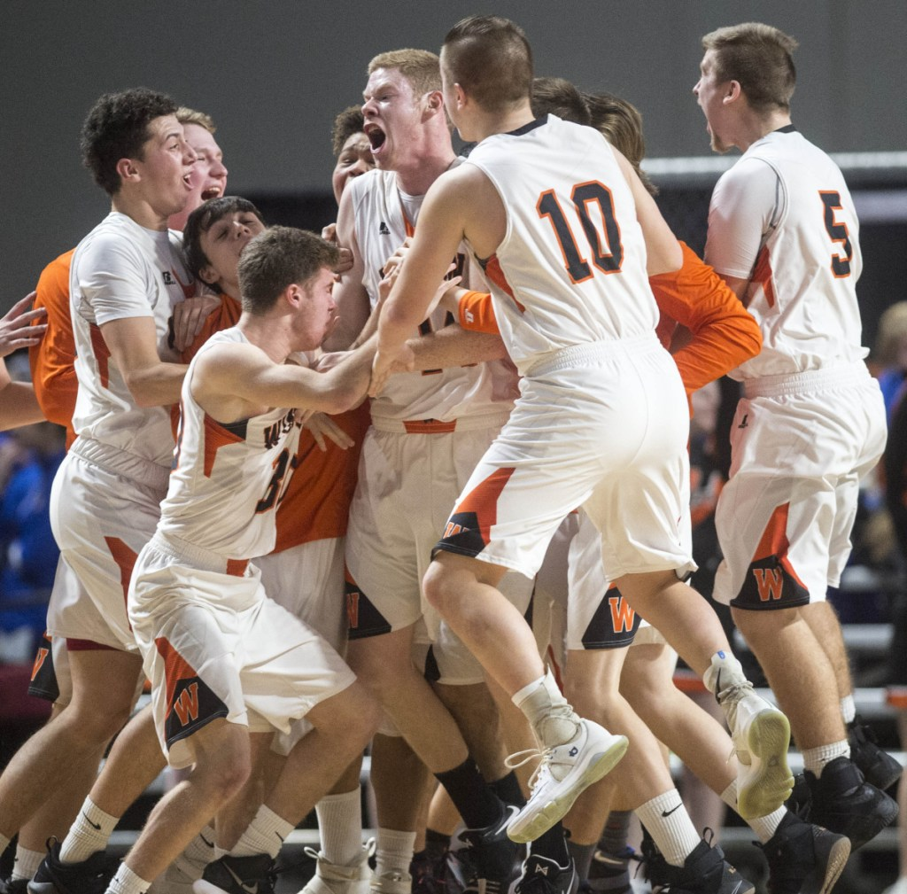 Jake Lapierre center, is swarmed by teammates after his game-winning shot to beat Oceanside 39-38 at the buzzer in the Class B North quarterfinals at the Cross Insurance Center in Bangor on Saturday.