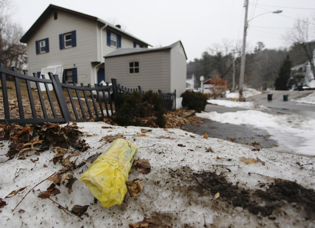 A plastic-wrapped newspaper lies uncollected in an Acorn Street yard in Biddeford. A regional group that advocates for freedom of the press has called on the city to alter rules it established late last year.