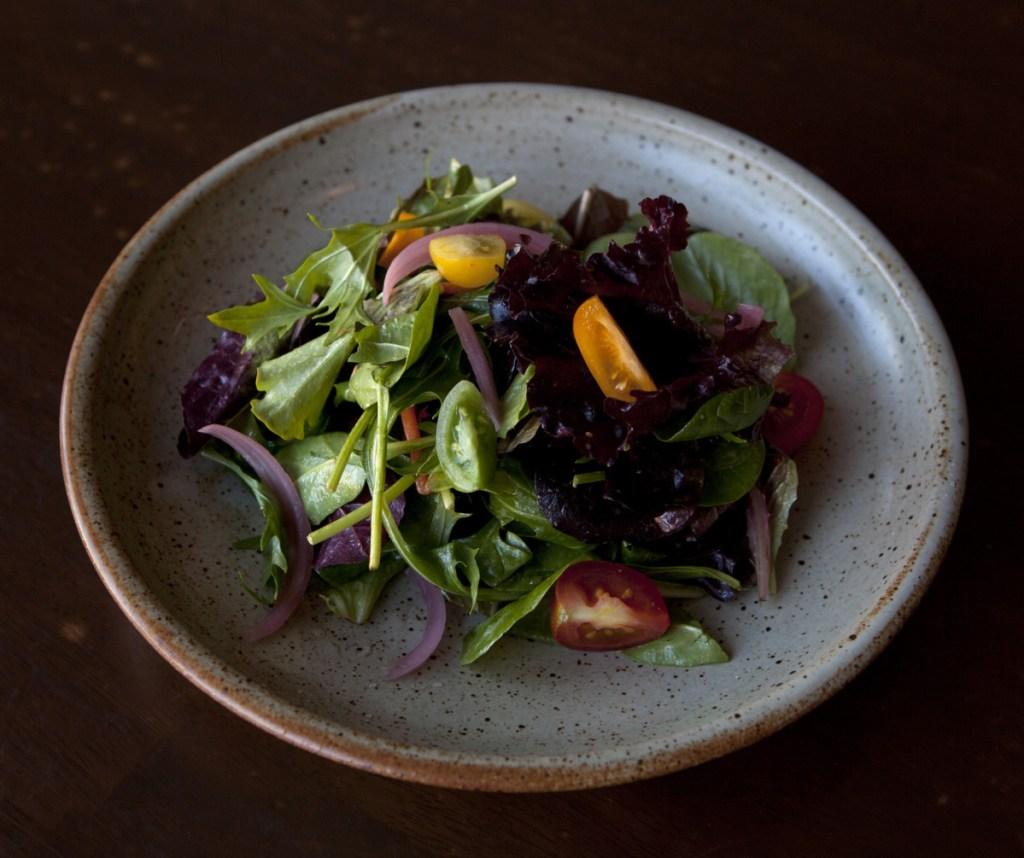 The house salad, with greens, carrots, peppers, pickled red onions and cherry tomatoes.