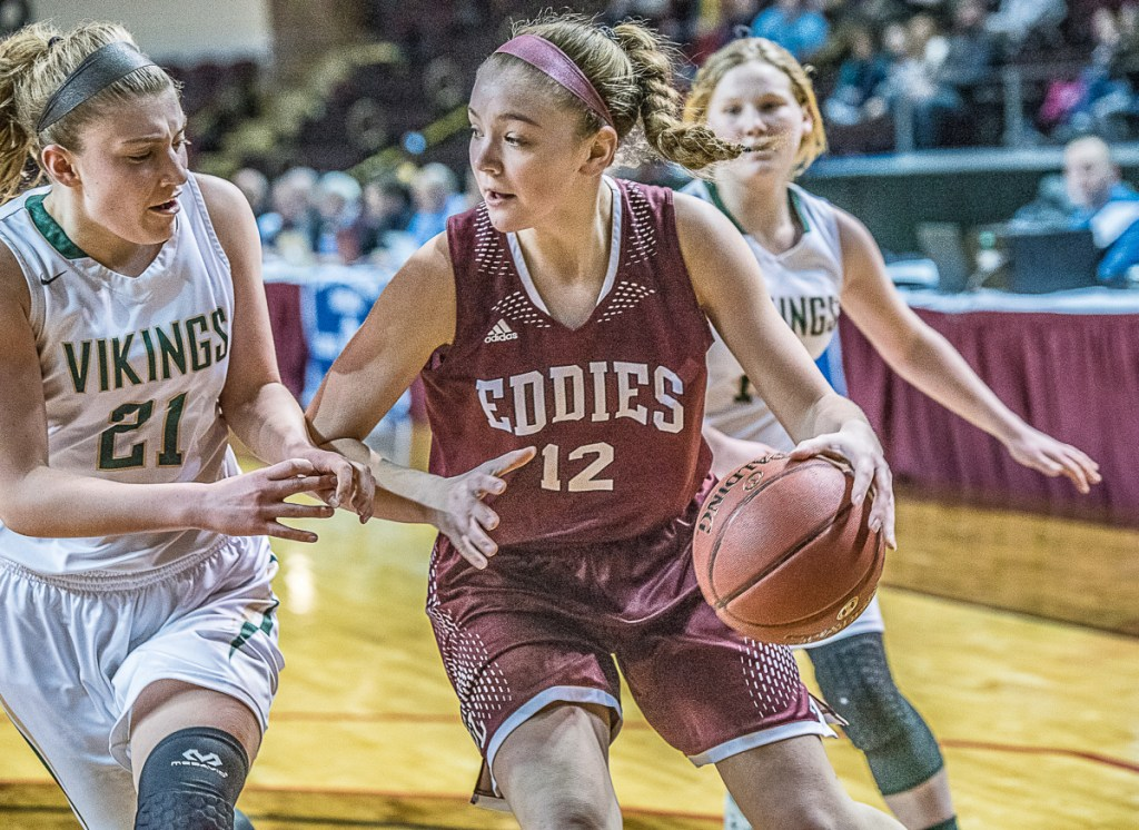 Edward Little's Jade Perry pushes past Oxford Hills' Maighread Laliberte during the Class AA North girls' basketball final at Cross Insurance Arena on Friday. (Andree Kehn/Sun Journal)