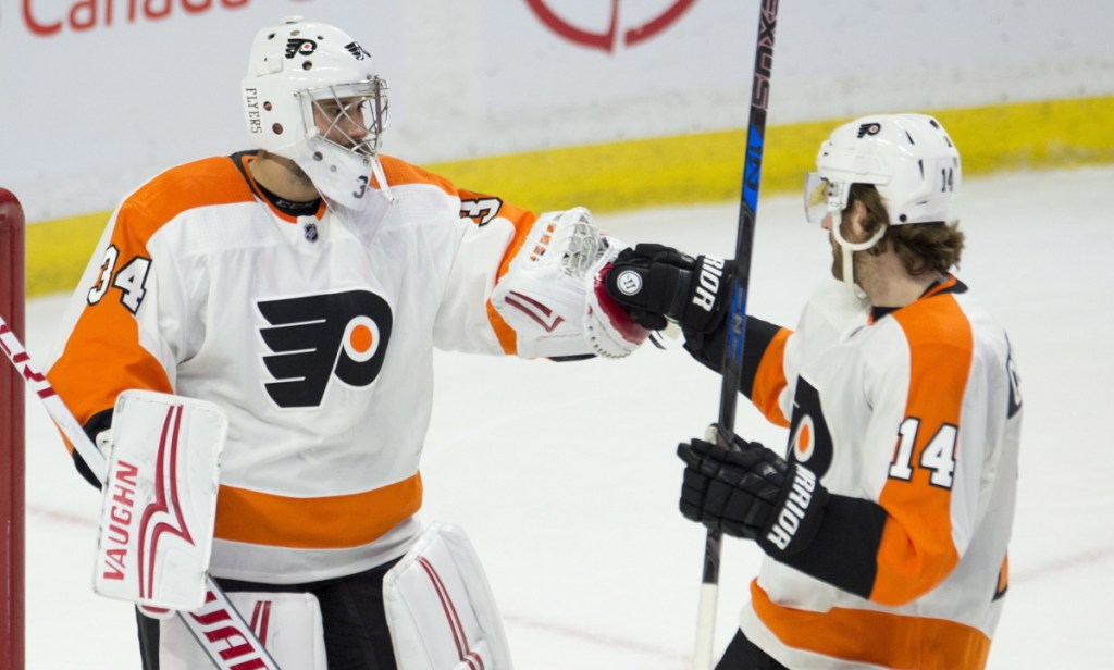 Goaltender Petr Mrazek, left, and Sean Couturier of Philadelphia celebrate Saturday after a 5-3 victory against the Ottawa Senators. It was Mrzek's second game with the Flyers.