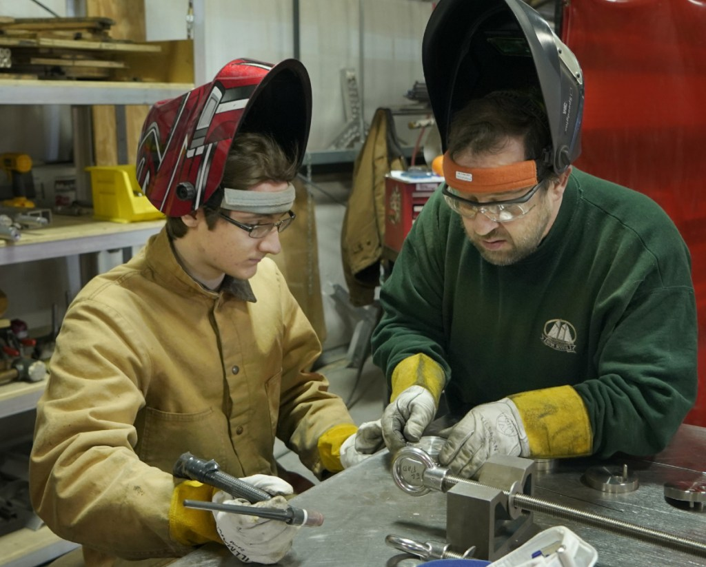 "Sam Roy, left, and Joe Woods prepare parts to be welded at DeepWater Buoyancy. Co-owner Matthew Henry said welders are in short supply. ""The best thing we can do for him is show him all the skills he'll need beyond welding,"" Henry said."