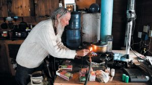 THIS PHOTO shows Billy Barr lighting his stove to make some tea at his remote cabin in Gothic, Colorado. Barr, who is a reclusive mountain man, has become a legendary citizen scientist who has been collecting a trove of invaluable data from his home.