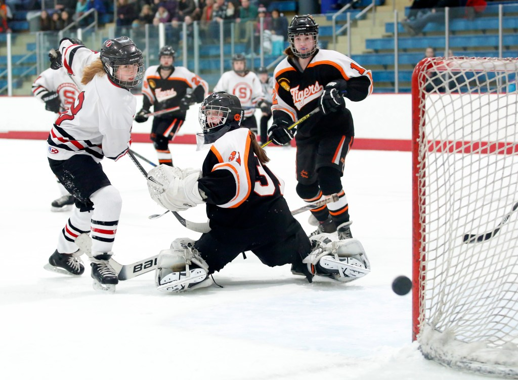 Carrie Timpson of Scarborough watches her shot narrowly miss the goal after tipping it over the shoulder of Biddeford goalie Trinity Atwater in the second period.