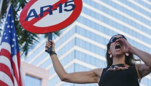 Alessandra Mondolfi holds a sign against AR-15 weapons as she yells, 'No More' during a protest against guns on the steps of the Broward County Federal courthouse in Fort Lauderdale, Fla., on Saturday, Feb. 17, 2018. Nikolas Cruz, a former student, is charged with killing 17 people at Marjory Stoneman Douglas High School in Parkland, Fla., on Wednesday. AP NEWSWIRE/Brynn Anderson
