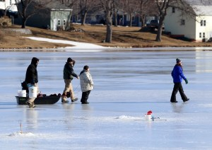 Several families, like this one, trekked across the ice at Number One Pond in Sanford Saturday to do a little ice fishing during Winterfest, the week-long series of events during school vacation week, sponsored by Sanford Parks and Recreation. Several youngsters won ribbons for the fish they caught. TAMMY WELLS/Journal Tribune