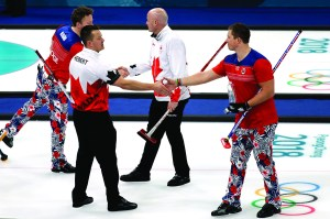 Norway's Christoffer Svae, right, shakes hands with Canada's Ben Herbert after their match at the 2018 Winter Olympics in Gangneung, South Korea, Thursday. At the Pyeongchang Olympics, curlers and their fans agree: In an era of vitriol and venom, curling may be the perfect antidote to our troubled times. AP NEWSWIRE
