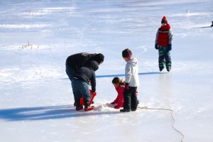Ryan Lovejoy Jr. and his father, also named Ryan Lovejoy, return the boy's 19 inch pickerel to the waters of Number One Pond after catching it on Saturday. The derby kicked off Winterfest, Sanford Parks and Recreation Department's vacation week series of events. TAMMY WELLS/Journal Tribune