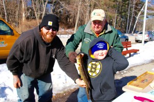 Ryan Lovejoy Jr., 6, caught the largest fish in the Winterfest Ice Fishing Derby held at Number One Pond in Sanford on Saturday — a big, 19 inch pickerel. He is shown here with his proud Dad, Rya Lovejoy, left, and Glenn