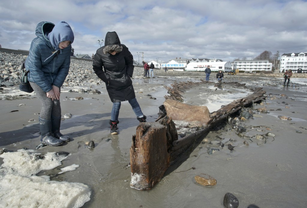 Rebecca Dugas, left, and Jayan Landry check out a shipwreck at Short Sands Beach in York on Monday. The shipwreck was uncovered over the past three days of coastal flooding. The last time it was revealed was in 2013. YORK, ME - MARCH 5: Rebecca Dugas, left, and Jayan Landry check out a shipwreck at Short Sands Beach in York on Monday. The shipwreck was uncovered over the past three days of coastal flooding. The last time it was revealed was in 2013. (Staff Photo by Gregory Rec/Staff Photographer)