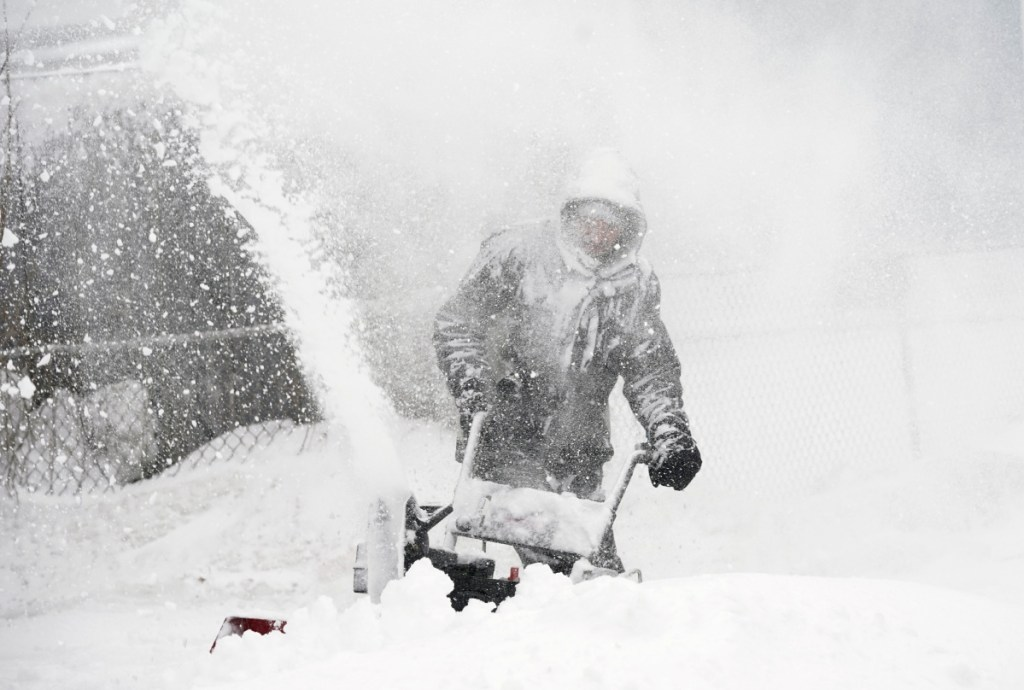 Kyle Binette feels the brunt of the storm as he clears snow from his driveway in Biddeford. Winds were gusting over 35 mph Tuesday.
