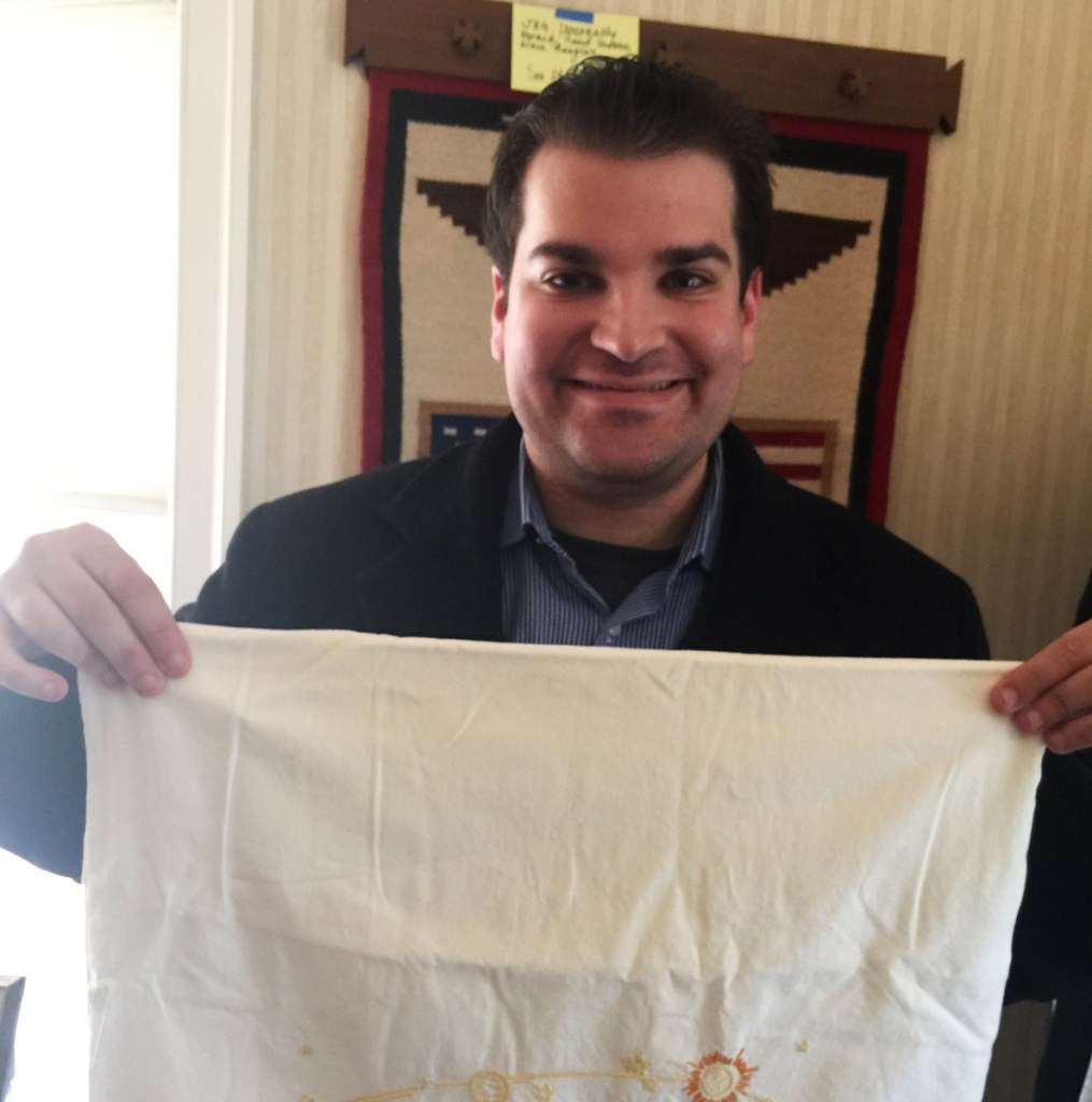 Adam Sackowitz displays an embroidered pillowcase with celestial bodies on it that belonged to the late senator and astronaut John Glenn.