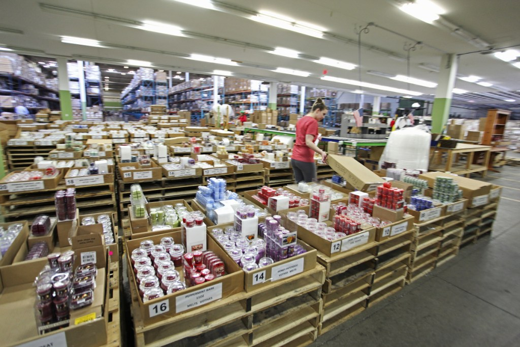 "Alicia Bennison restocks in the internet sales department at Village Candle. The company has started a major export push, building on a toehold in the United Kingdom and continental Europe. ""The international market is huge. We think it can be equivalent to the U.S. market for us in three to five years,"" President Jeanne Hulit said Monday."