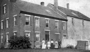 FAMILY MEMBERS outside the jailer's residence and jail, Wiscasset, circa 1900.