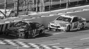CLINT BOWYER (14) passes Ryan Blaney (12) for the lead during a NASCAR Cup Series auto race at Martinsville Speedway in Martinsville, Virginia, on Monday.