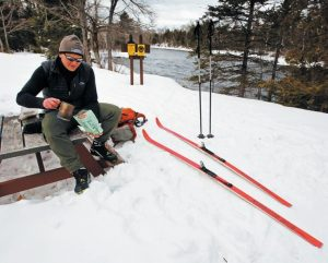 TOM MCDONALD OF SOUTH PORTLAND pours hot water into a backpacker's meal during a lunch break along the east branch of the Penobscot River in the Katahdin Woods and Waters National Monument in northern Maine earlier this month. The scenic wintertime river views are popular among those willing to put in the effort on skis or snowshoes. There is no fee to access the park's ski trails.