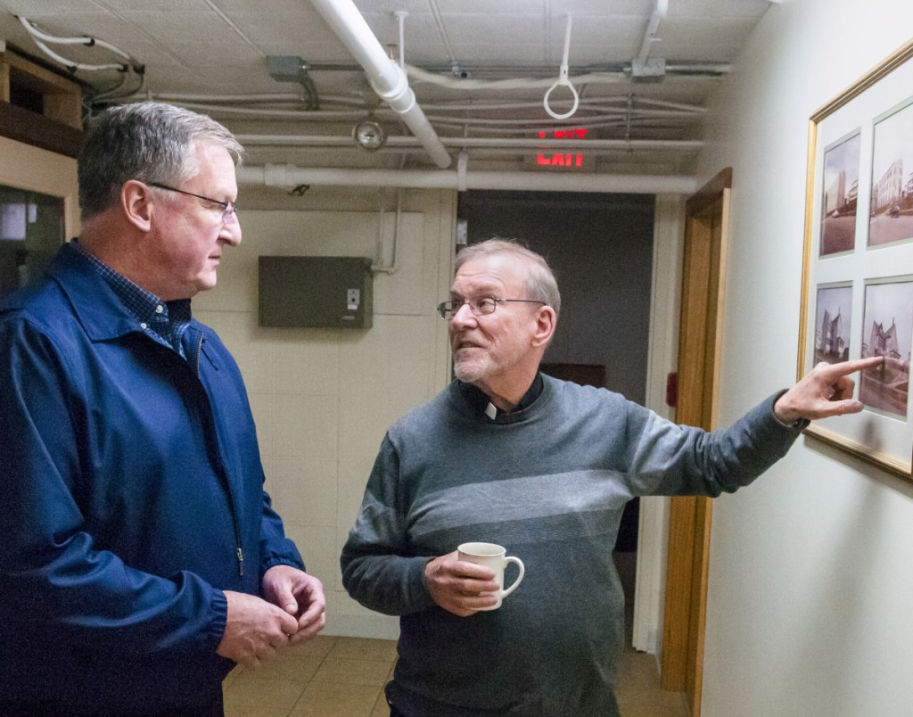 The Rev. John Skehan, left, looks at historical photos with the Rev. Frank Morin during a tour of the St. Michael Pastoral Center on Thursday in Augusta. Skehan will be replacing Morin, who plans to retire July 1. The Pastoral Center is in the former St. Augustine's School building.
