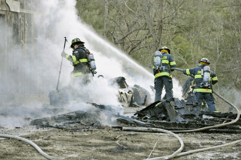 Firefighters extinguish hot spots Saturday after battling a fatal blaze in West Falmouth.