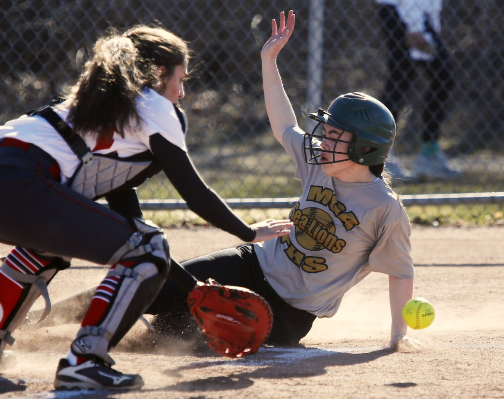 Holly Akey of Maine Girls' Academy slides into the plate, beating a throw to South Portland catcher Ashley Aceto in the first inning of South Portland's 16-10 victory Monday.