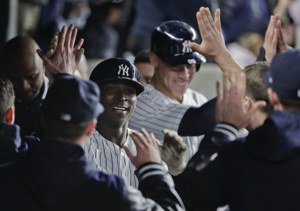The Yankees' Didi Gregorius, center left, is congratulated by teammates in the dugout after driving in Aaron Judge, center right, with a two-run homer against the Twins on Tuesday night.
