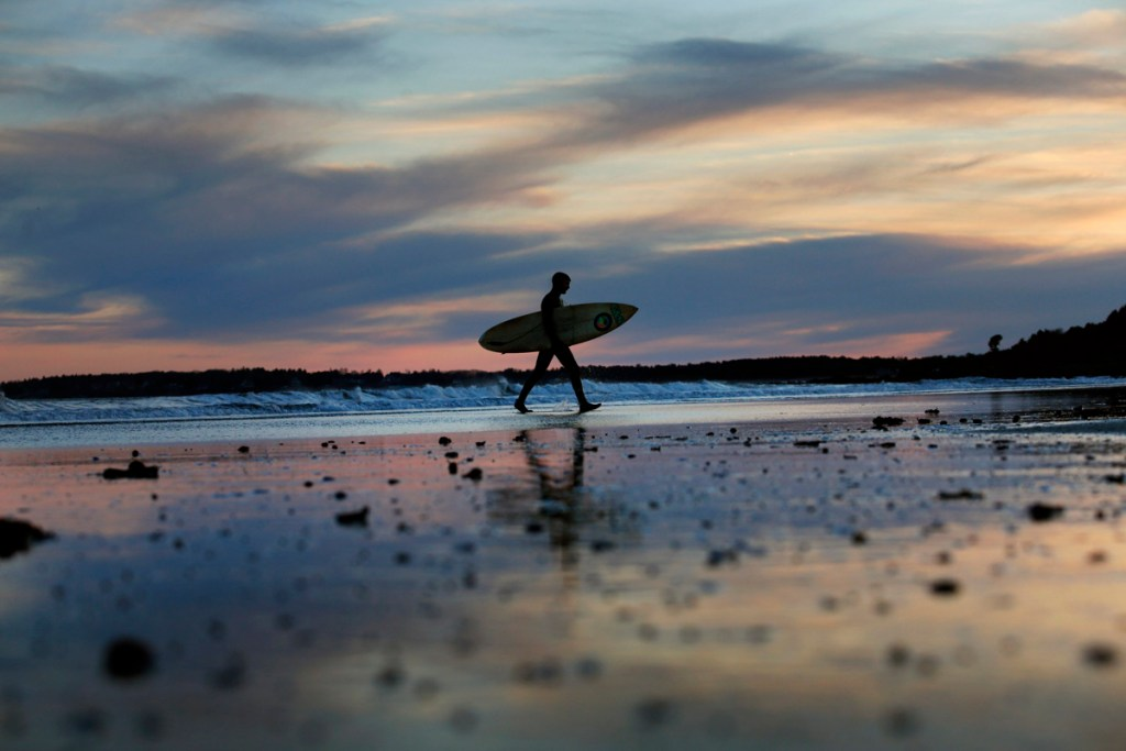 Chris Pickles of Scarborough walks along Higgins Beach after surfing in March, 2017.