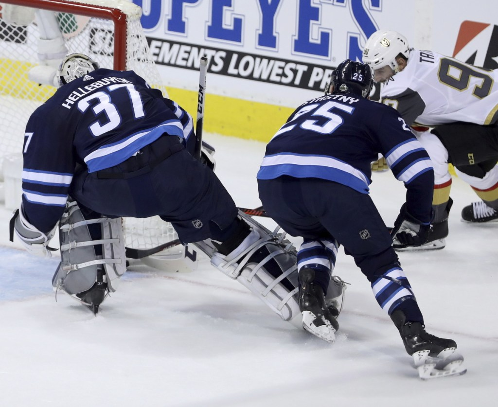 Las Vegas' Tomas Tatar, right, scores on Winnipeg goalie Connor Hellebuyck, left, with Paul Stastny on Monday in Winnipeg, Manitoba. The game was in progress at deadline.