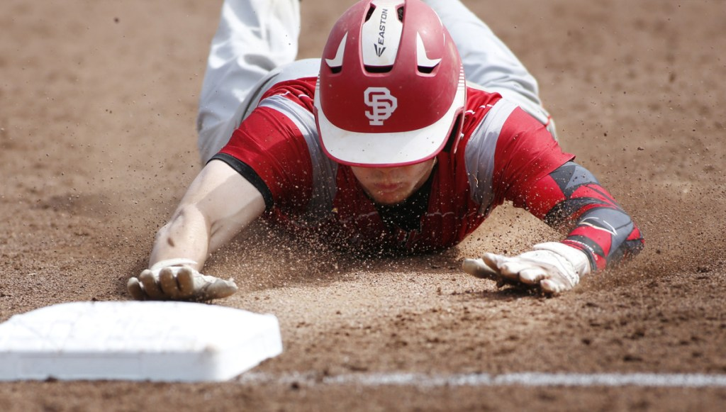 Riley Hasson of South Portland slides safely into third base during Saturday's game against Portland at Hadlock Field. The Red Riots allowed a run for the first time in five game but improved to 10-2.