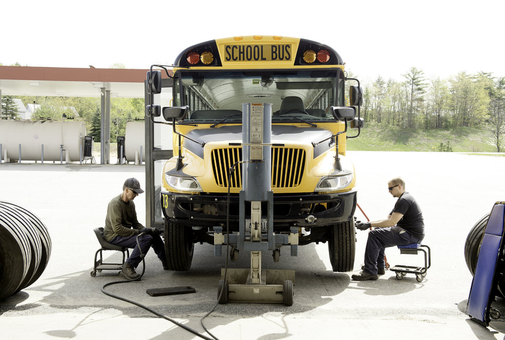 Bus mechanics Rob Sawyer, left, and his son Tyler Sawyer change the front two tires on school bus No.13 at the Regional School Unit 16 bus garage in Poland on Thursday.