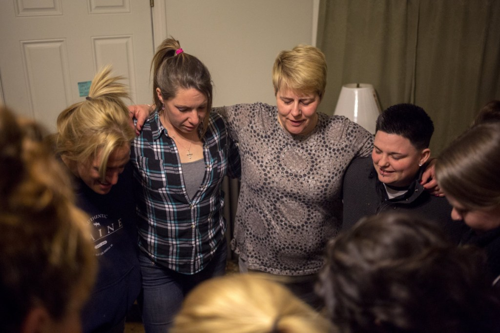 Nichole Curtis, center, who runs a Portland sober house, takes part in the prayer at the end of a March 2017 meeting. A bill before the U.S. House would allow cities to bar those in recovery from cohabitating in residential neighborhoods.