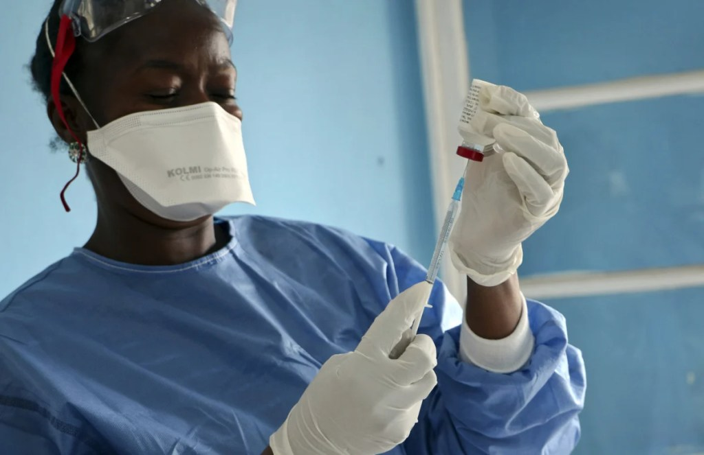 A health care worker cleans a colleague wearing Personal Protective Equipment at an Ebola treatment center in Coyah, Guinea, in 2015. At left, a World Health Organization medic prepares vaccines to give to front line aid workers, in Mbandaka, Congo, on May 30. For the first time since the Ebola virus was identified more than 40 years ago, a vaccine has been dispatched to the front lines to try to curb the current epidemic in Congo.