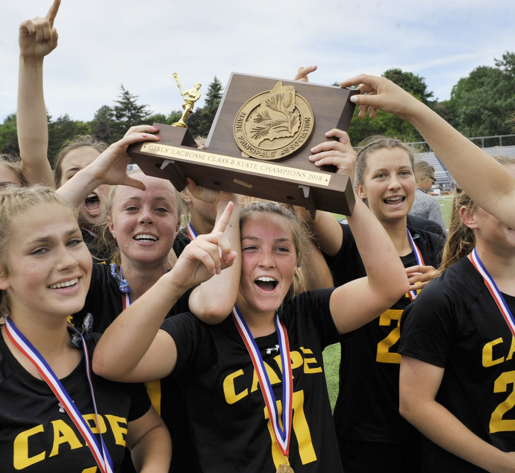 Cape Elizabeth's Cloe Chapin holds the Class B state championship plaque and celebrates with teammates after they won the state title Saturday in Portland.