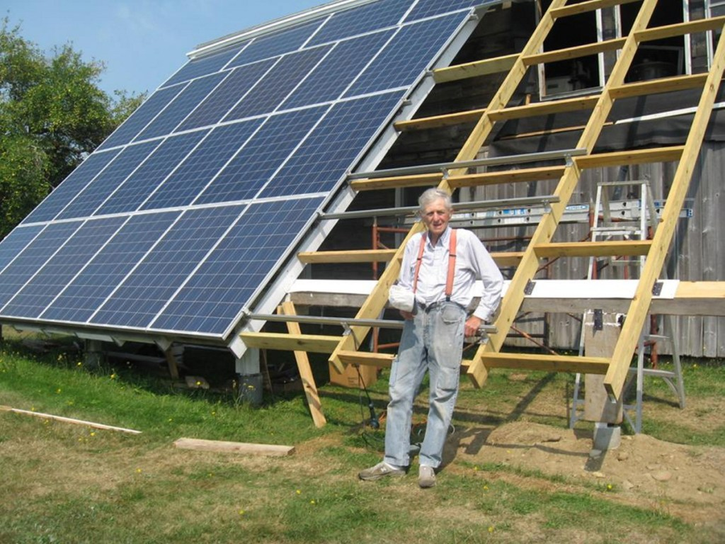 """The humble Farmer finishes up the rack for his last eight solar panels. He now has 30 of them; his monthly electric bill is about $10 """"for the convenience of being hooked to the grid."""""""