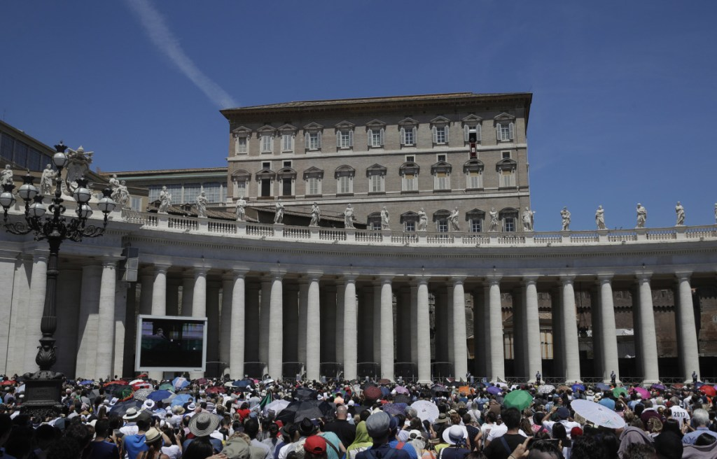 Faithful listen to Pope Francis as he recites the Angelus noon prayer from the window of his studio overlooking St. Peter's Square, at the Vatican on Sunday, June 17.