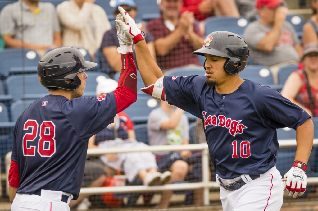 Portland designated hitter Luke Tendler, right, is congratulated by teammate Austin Rei after Tendler hit a solo home run in seventh inning during the Sea Dogs' 5-4 win over the Trenton Thunder on Sunday at Hadlock Field.