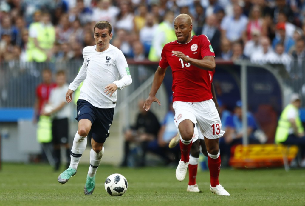 France's Antoine Griezmann vies for the ball with Denmark's Mathias Jorgensen during the group C match between Denmark and France at the 2018 World Cup in Moscow on Tuesday.  The teams played to a scoreless draw and drew boos and whistles from the crowd.