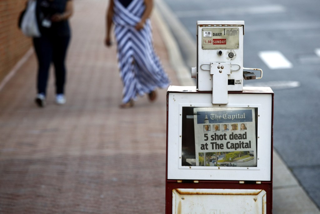 A Capital Gazette newspaper rack displays the day's front page on Friday in Annapolis, Maryland. A man armed with smoke grenades and a shotgun attacked journalists in the newspaper's building Thursday, killing several people before police quickly stormed the building and arrested him, police and witnesses said.