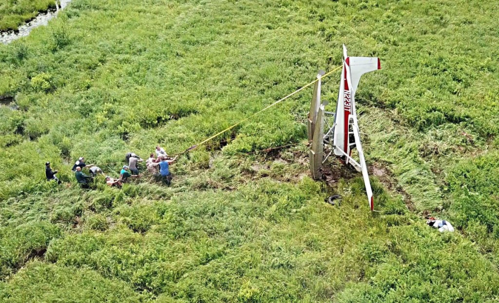 About a dozen men work to flip the crashed plane right-side up before pulling it to Route 126 on Sunday.