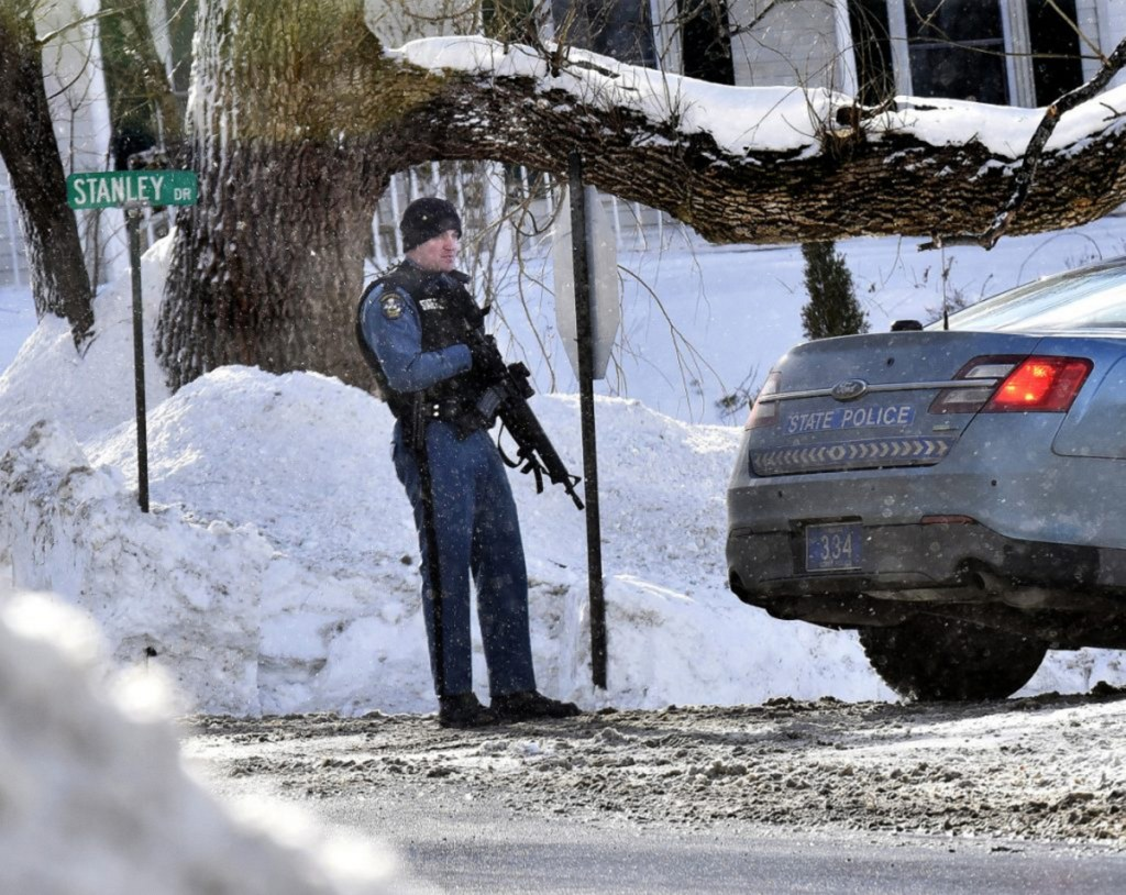 A Maine State Trooper with an assault rifle stands guard in January at one end of Stanley Drive in Norridgewock as police search for a suspect in an armed robbery at the nearby Skowhegan Savings Bank branch.